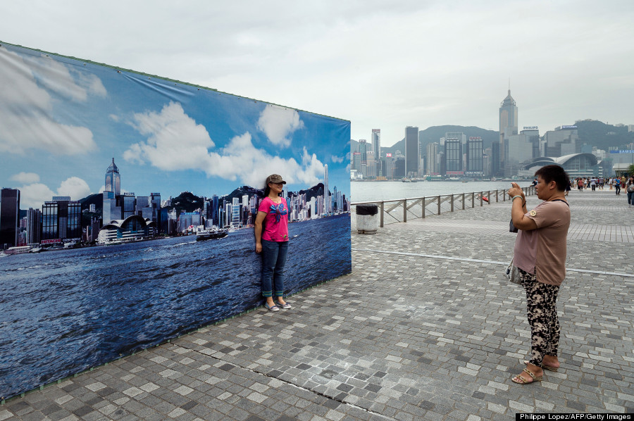 A tourist has her picture taken during a cloudy day in front of a billboard featuring photos of the city skyline with a clear sky in Hong Kong on August 30, 2013. The billboard erected along the Avenue of Stars attracts tourists who find it more appealing to pose for photographs in front of it than the city's skyline on a cloudy or polluted day.   AFP PHOTO / Philippe Lopez        (Photo credit should read PHILIPPE LOPEZ/AFP/Getty Images)